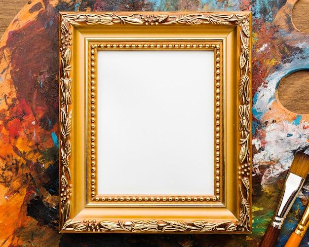 Skopiuj płótno przestrzeni w złotej ramie i farby