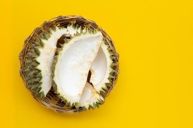 Skórka durian w bambusowym koszu na zielonym tle. widok z góry