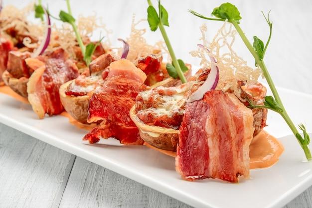 Skórka ziemniaka z boczkiem i serem i sosem pomidorowym na drewnianym stole