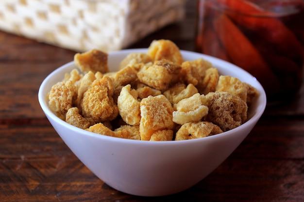 Skórki wieprzowe (torresmo) smażone w ceramicznej misce na rustykalnym drewnianym stole w restauracji. typowe danie kuchni brazylijskiej i azjatyckiej