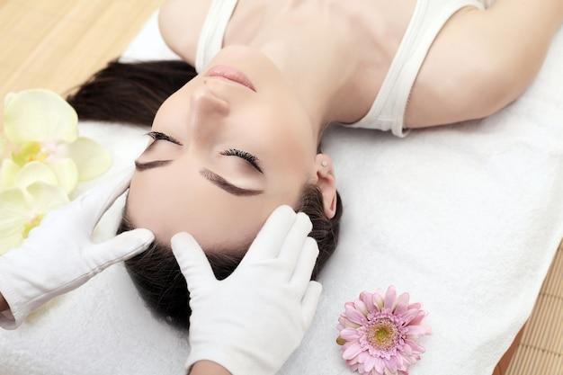 Skóry i ciała opieka, zakończenie młoda kobieta dostaje zdroju traktowanie przy piękno salonem, zdrój twarzy masaż