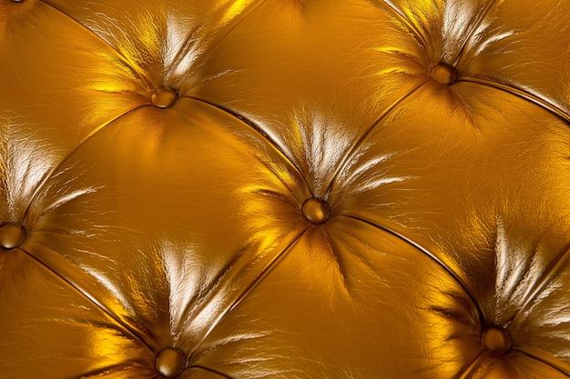 Skórzana tekstura wyściełana guzikami na złotym tle. meble, tapicerka, dekoracja, koncepcja projektowa.