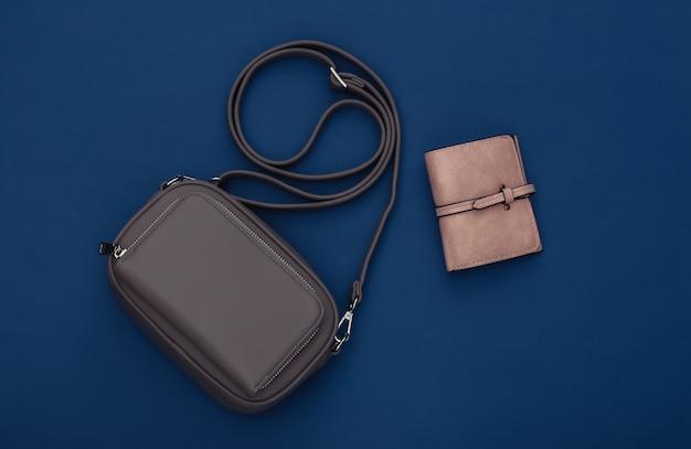 Skórzana torba i portfel na klasycznym niebieskim tle. kolor 2020. widok z góry.