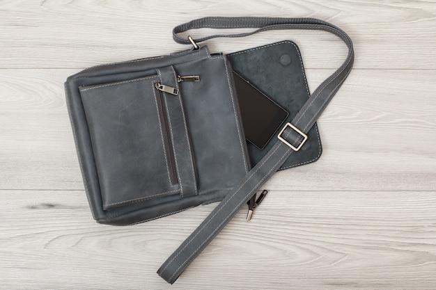 Skórzana torba na ramię dla mężczyzn z telefonem komórkowym z szarym drewnianym tłem. akcesoria męskie. widok z góry