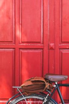 Skórzana torba na rowerze przed czerwonymi drzwiami