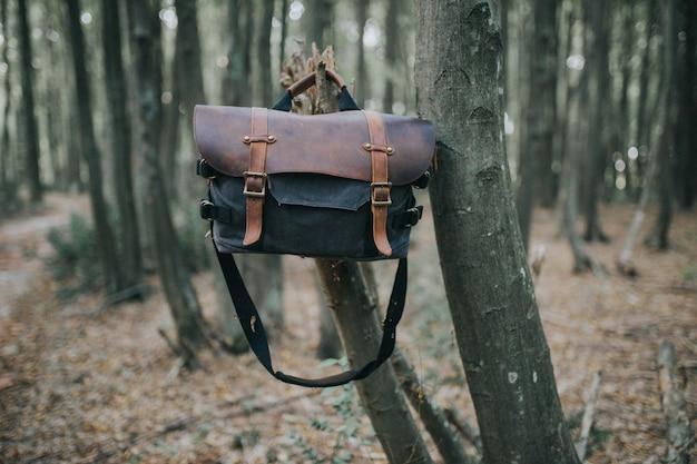 Skórzana torba na wędrówki wisząca na gałęzi drzewa w lesie