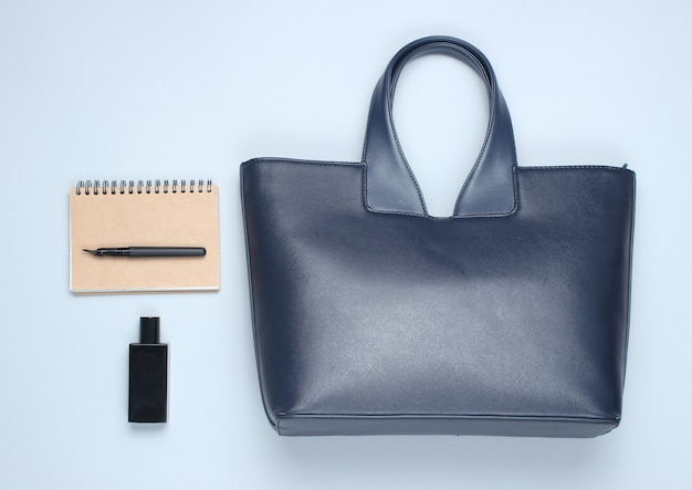 Skórzana torba, notatnik, butelka perfum na szarym stole. akcesoria biznesowe i modowe. widok z góry, minimalizm
