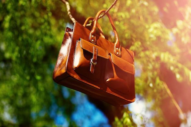 Skórzana torba retro brązowy człowiek w jasny kolorowy letni park wisi na leafes