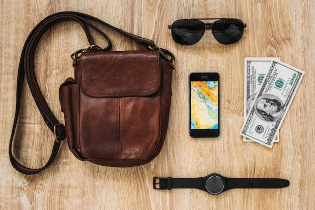 Skórzana torba, smartfon, okulary przeciwsłoneczne, zegarek, pieniądze. akcesoria męskie. strój podróżnika, studenta, nastolatka, młodej kobiety lub faceta.