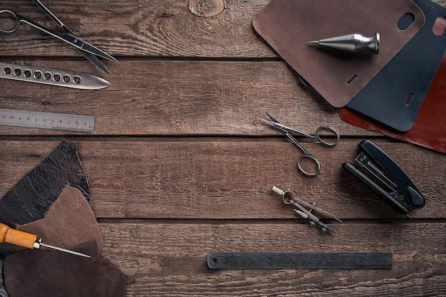 Skórzana torebka. miejsce pracy rzemieślnika w warsztacie. miejsce na twój tekst lub logo. idealny na bloga. widok z góry