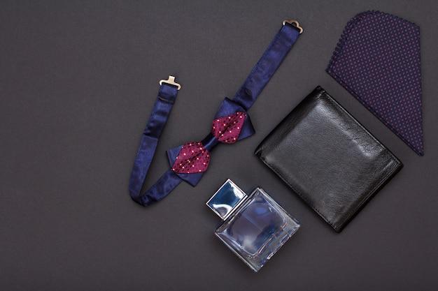 Skórzana torebka, woda kolońska dla mężczyzn, chusteczka i muszka na czarnym tle. akcesoria dla mężczyzn. widok z góry.