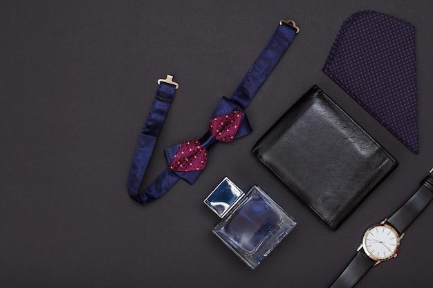 Skórzana torebka, zegarek z czarnym skórzanym paskiem, woda kolońska dla mężczyzn, chusteczka i muszka na czarnym tle. akcesoria dla mężczyzn. widok z góry.