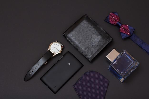 Skórzana torebka, zegarek z czarnym skórzanym paskiem, woda kolońska dla mężczyzn, muszka, telefon komórkowy i chusteczka na czarnym tle. akcesoria dla mężczyzn. widok z góry.