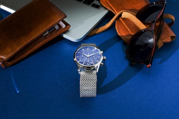 Skórzana torebka, zegarek z metalową bransoletą, okulary przeciwsłoneczne i laptop na niebieskim tle. akcesoria dla mężczyzn. widok z góry