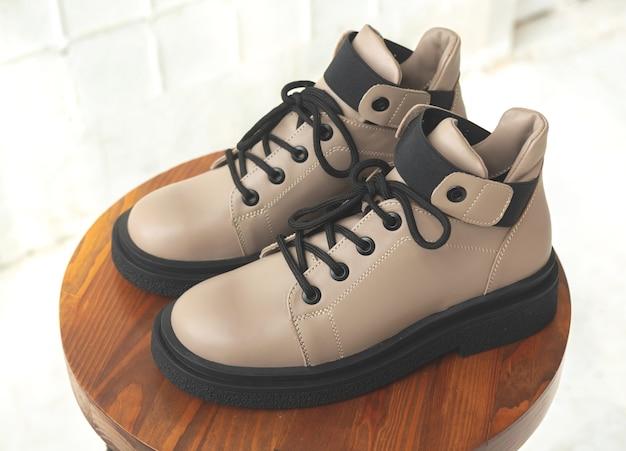 Skórzane buty damskie. kobiece obuwie jesienno-zimowe na drewnianym stojaku. nowoczesne zdjęcie projektowe