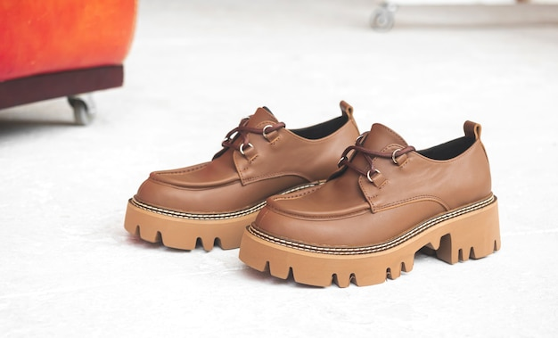 Skórzane buty damskie lub trampki na betonowym tle w studio