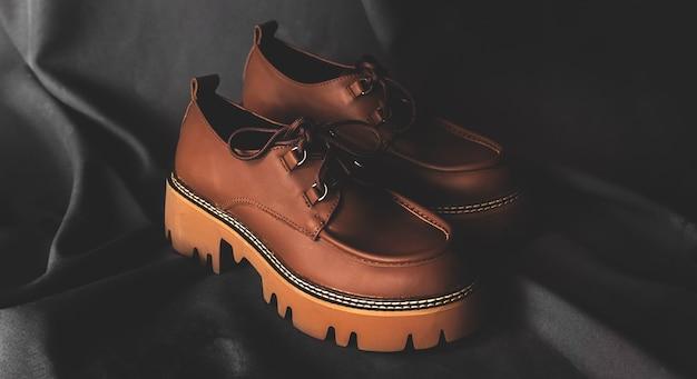 Skórzane buty damskie w stylu vintage na czarnym tle, koncepcja mody i klasycznego obuwia oraz zdjęcie projektu