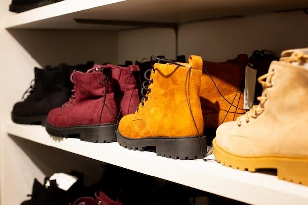 Skórzane buty na półkach z bliska. buty damskie w sezonie jesiennym. sprzedaż obuwia skórzanego damskiego. licznik z butami