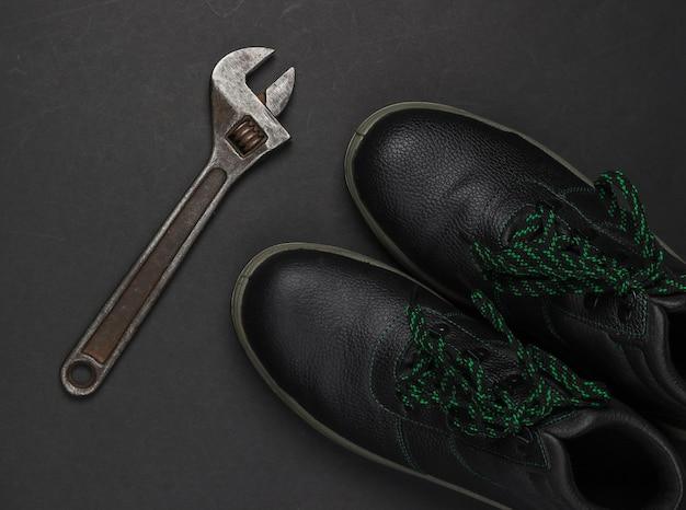 Skórzane buty robocze i klucz nastawny na czarnym tle