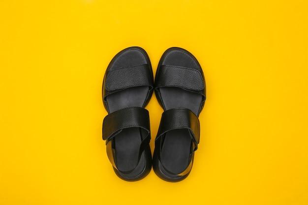 Skórzane czarne sandały damskie na żółtym tle. widok z góry. płaskie ułożenie