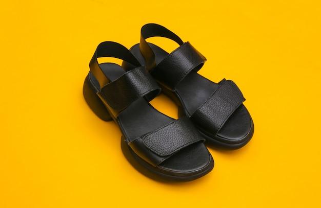 Skórzane czarne sandały damskie na żółtym tle.