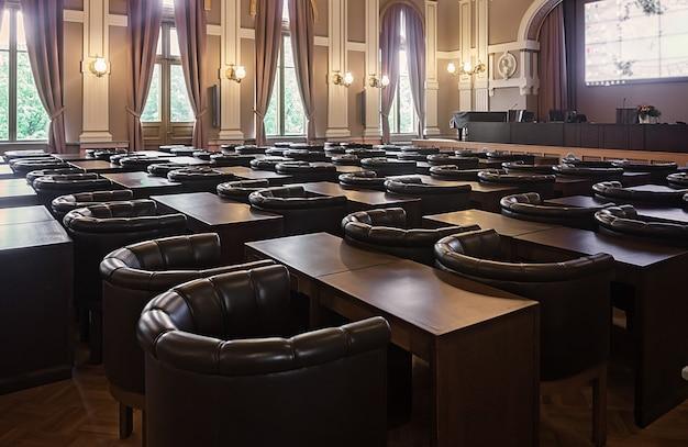 Skórzane fotele i drewniane stoły w sali konferencyjnej