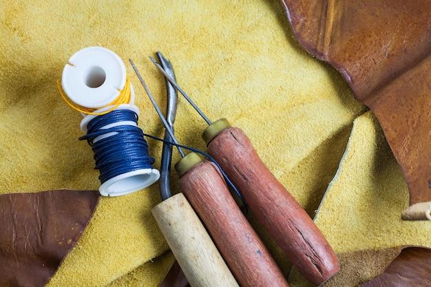 Skórzane narzędzia do szycia na tle prawdziwej skóry.