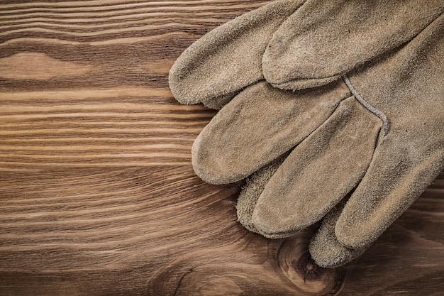 Skórzane rękawice ochronne na koncepcji budowy rocznika drewnianej deski
