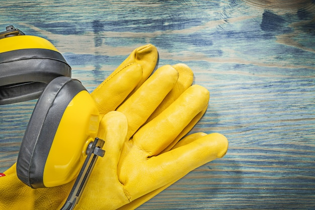 Skórzane rękawice ochronne nauszniki redukujące hałas na drewnianej konstrukcji deski