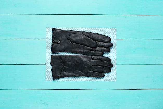 Skórzane rękawiczki na niebieskiej drewnianej powierzchni.