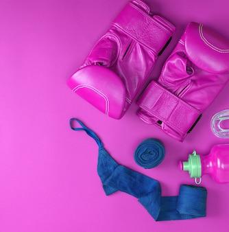 Skórzane różowe rękawice bokserskie, niebieski bandaż tekstylny