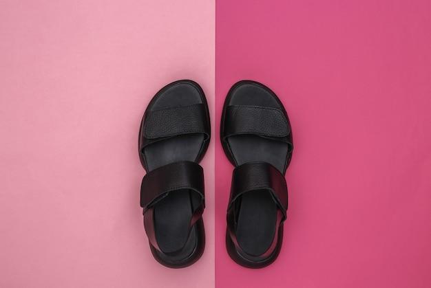 Skórzane sandały damskie czarne na różowym tle. widok z góry. płaskie ułożenie