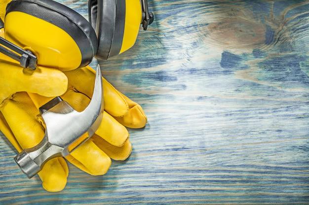 Skórzane żółte rękawice ochronne nauszniki pazur młotek na koncepcji konstrukcji drewnianej deski