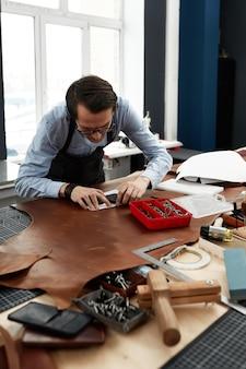 Skórzani rzemieślnicy pracujący przy tworzeniu measupenets we wzorach przy stole w pracowni warsztatowej.
