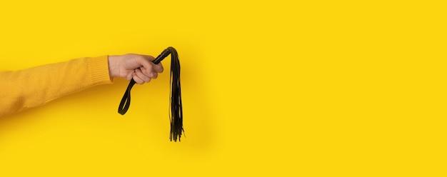Skórzany bicz w dłoni na żółtym tle, akcesoria bdsm, układ panoramiczny