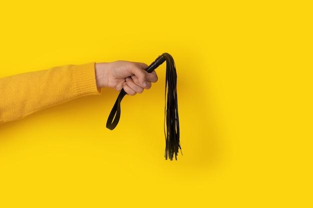 Skórzany bicz w dłoni na żółtym tle, akcesoria bdsm