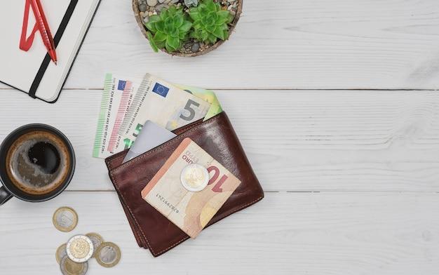 Skórzany męski otwarty portfel z banknotami euro, monetami i kartą kredytową na białym drewnianym układzie stołu z miejscem na kopię planowanie zakupów i wydatków filiżanka kawy i notatnik obok stołu