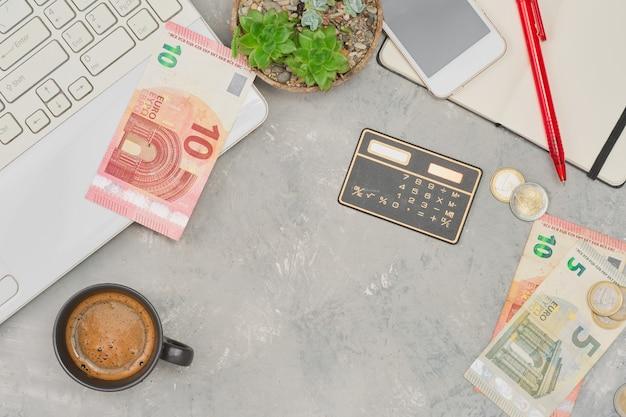 Skórzany męski otwarty portfel z monetami banknotów euro na białym drewnianym stole zbliżenie selektywne skupienie płytka głębia ostrości planowanie zakupów i wydatków laptop i notatnik obok stołu
