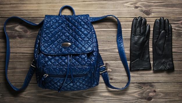 Skórzany modny plecak, rękawiczki na drewnianej powierzchni.