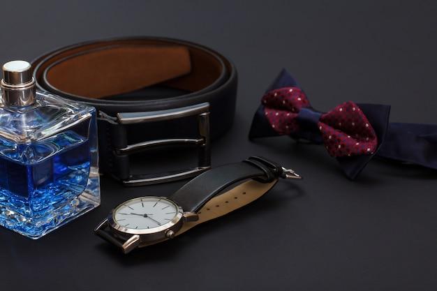 Skórzany pasek z metalową klamrą, zegarek z czarnym skórzanym paskiem, muszka i woda kolońska dla mężczyzn na czarnym tle. akcesoria dla mężczyzn.