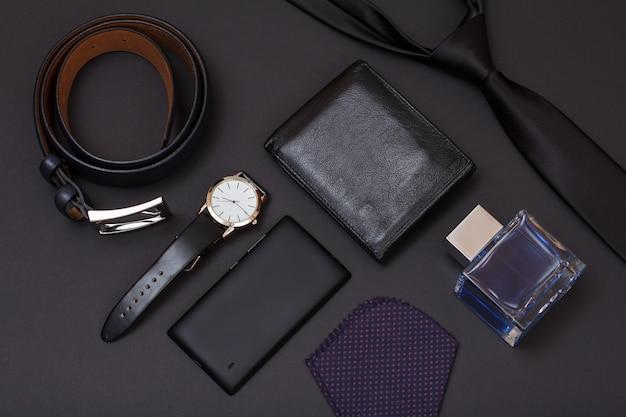Skórzany pasek z metalową klamrą, zegarek z czarnym skórzanym paskiem, telefon komórkowy, woda kolońska dla mężczyzn, torebka, krawat i chusteczka na czarnym tle. akcesoria dla mężczyzn.