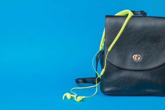 Skórzany plecak damski i żółte słuchawki na niebieskim tle. pojęcie turystyki i edukacji.