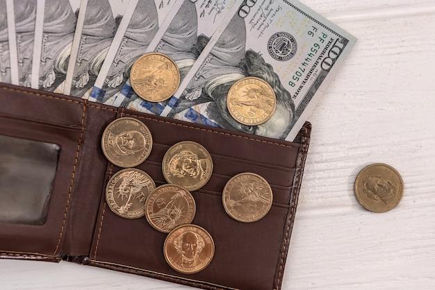 Skórzany portfel z dolarem amerykańskim i centem na białym drewnianym biurku, koncepcja finansów
