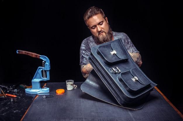 Skórzany rzemieślnik tworzy nową galanterię skórzaną w miejscu pracy.