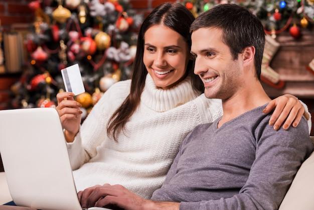 Skorzystanie z wyprzedaży świątecznych. piękna młoda para kupująca online podczas korzystania z komputera z choinką w tle