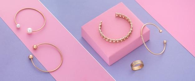 Skośny kolaż zdjęć złotych bransoletek i pierścionka na tle pastelowych kolorów
