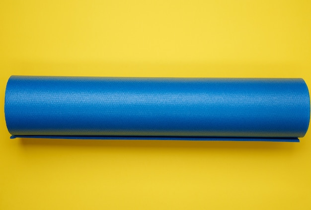 Skręcana niebieska mata neoprenowa do jogi i sportów na żółtej powierzchni