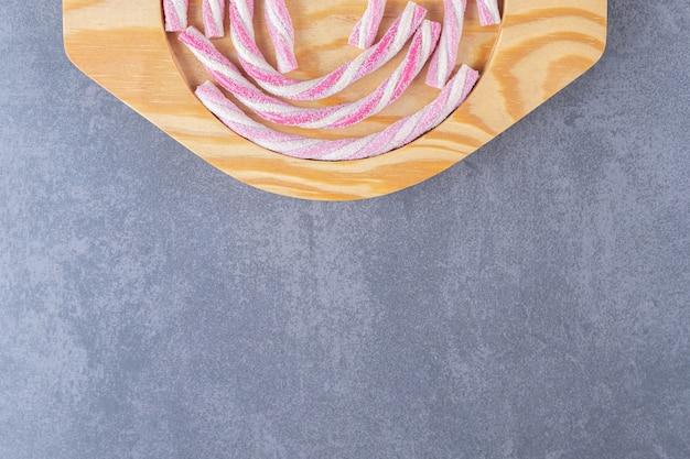 Skręcone pianki na drewnianym talerzu, na marmurze.