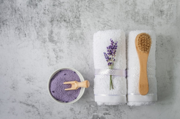 Skręcone ręczniki kąpielowe z solą do kąpieli i szczotką w kolorze jasnoszarym.