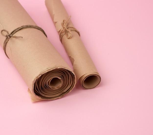 Skręcone rolki brązowego papieru na różowej powierzchni